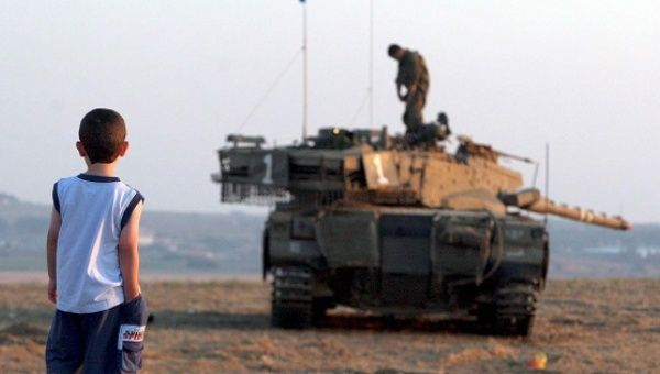 A child looks at an Israeli tank near Gaza, July, 2006. The International Criminal Court will consider Palestine
