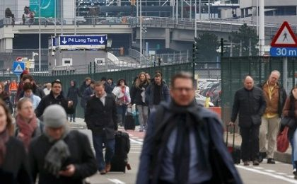 People leave the scene of explosions at Zaventem airport near Brussels, Belgium.
