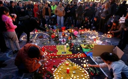 People gather around a memorial in Brussels following bomb attacks in Brussels, Belgium.