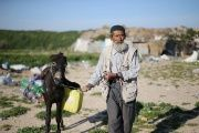 A Palestinian man pulls his donkey as he makes his way to fill bottles and jerrycan with drinking water in Khan Younis in the southern Gaza Strip, March 1, 2016.