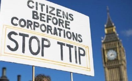 A woman holds a sign protesting the TTIP trade deal