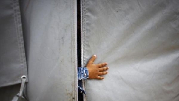 A Kurdish refugee boy from the Syrian town of Kobani sticks his hand out of a tent in a refugee camp in the border town of Suruc, Sanliurfa province.