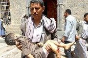 A man carries the body of a child out of the mosque which was attacked by a suicide bomber in Sanaa.