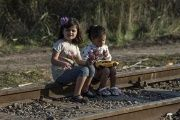 Syrian refugee girls sit on a railway track on the Serbian border with Hungary near the village of Horgos, Aug. 28, 2015.