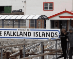 Argentine Malvinas War veterans Hugo Romero (R) and Walter Sarverry walk next to a ''Welcome to the Falkland Islands'' sign in Port Stanley, March 14, 2012.