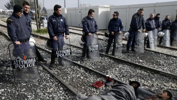 Migrants block a railway during a protest demanding the opening of the border between Greece and Macedonia in Idomeni, Greece, Tuesday, March 22, 2016.