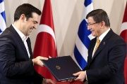 Turkish Prime Minister Ahmet Davutoglu (R) and his Greek counterpart Alexis Tsipras exchange agreements during a signing ceremony in the Aegean port city of Izmir, western Turkey, March 8, 2016.