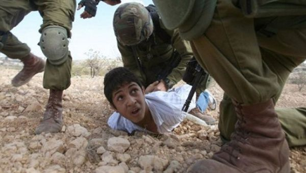 A Palestinian youth is arrested by Israeli soldiers during a protest.