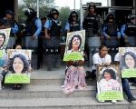 Indigenous people hold posters of Berta Caceres while sitting in front of riot police during a protest to demand justice in Tegucigalpa, Honduras, March 17, 2016.