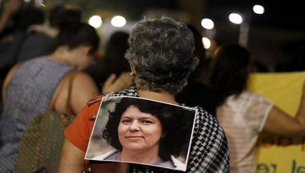 An activist wears a photo of slain environmental rights activist Berta Caceres during a protest to mark International Women