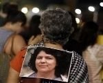 An activist wears a photo of slain environmental rights activist Berta Caceres during a protest to mark International Women's Day March 8, 2016.