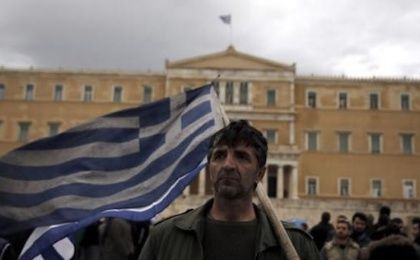 A farmer carries a Greek flag in front of the parliament during a protest against planned pension reforms in Athens, Greece February 12, 2016.
