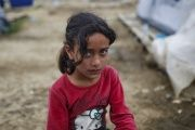 A child looks on at a makeshift camp for migrants and refugees at the Greek-Macedonian border near the village of Idomeni