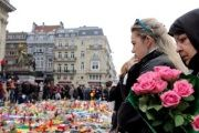 People observe a minutes silence at a street memorial to victims of the bombings in Brussels, Belgium, March 24, 2016