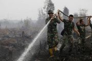 Indonesian soldiers spray water on peatland fire in Pulang Pisau regency east of Palangkaraya, Central Kalimantan, Indonesia in this Oct. 29, 2015.