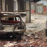 A woman passes a destroyed car March 28,1999, after a NATO missile hit downtown of Kosovo