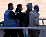 Frontex officers escort migrants boarding on a Turkish-flagged passenger boat to be returned to Turkey, on the Greek island of Lesbos, April 4, 2016.