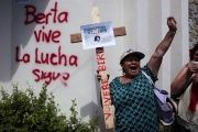 A woman holds a cross with a sign featuring Berta Caceres that says,