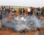 Rebel fighters and civilians gather around the wreckage of a Syrian warplane that was shot down in the Talat al-Iss area, south of Aleppo, Syria April 5, 2016