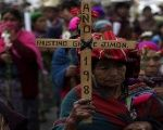 An Indigenous woman holds a cross during a march to commemorate the National Day of Dignity for the Victims of Armed Internal Conflict.