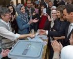 Syria's President Bashar Assad receives his identification card next to his wife Asma (to his right), after casting their votes, inside a polling station during parliamentary elections in Damascus, Syria on April 13, 2016.