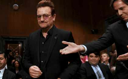 U.S. Deputy Secretary of State Antony Blinken (R) welcomes U2 lead singer Bono to testify before a Senate Appropriations State, Foreign Operations and Related Programs Subcommittee hearing.