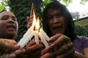 Activists light candles and offer prayers during a memorial ceremony in Manila.