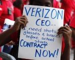 A girl holds a sign at a protest with Verizon employees.