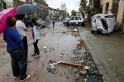 People look on as debris is seen along a street in Dolores, the day after the city was hit by a tornado.