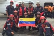 A Venezuelan rescue team poses for a photo as they prepare to board a plane to Ecuador to join rescue efforts after a massive earthquake, Sunday April 17, 2016.