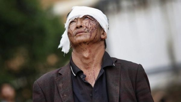 An injured man looks up as he walks next to debris after an earthquake hit Ludian county, Yunnan province August 4, 2014.