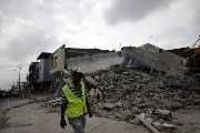 A worker walks past a collapsed building after an earthquake struck off the Pacific coast, in Guayaquil, Ecuador, April 17, 2016.