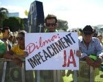 Protesters support the impeachment of Rousseff with a sign reading,