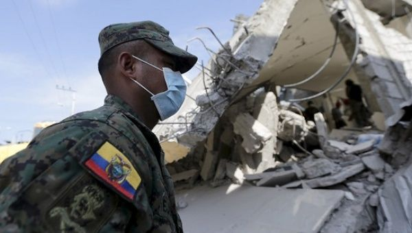 A soldier walks past a collapsed building after an earthquake struck off the Pacific coast, in Pedernales, Ecuador.