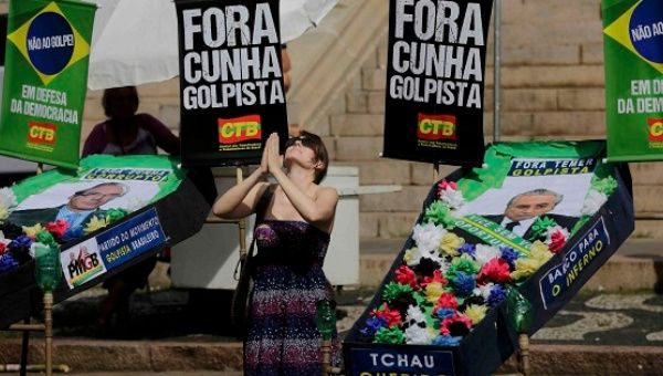 "A protester kneels with mock coffins of house speaker Eduardo Cunha and Vice President Michel Temer with ""Out coup-plotter"" signs in Porto Alegre, April 17, 2016."