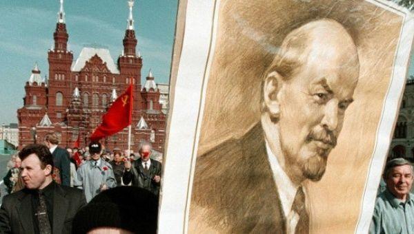 Demonstrator holds picture of Vladimir Lenin, founder of Soviet Union.