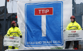 Greenpeace activists display a banner as they block the main entrance of a conference center where negotiators are expected to discuss the 12th Round of the TTIP trade deal.