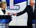 Hillary Clinton reacts as rival candidate Bernie Sanders tries to hand her a piece of paper during a Democratic debate hosted by CNN.