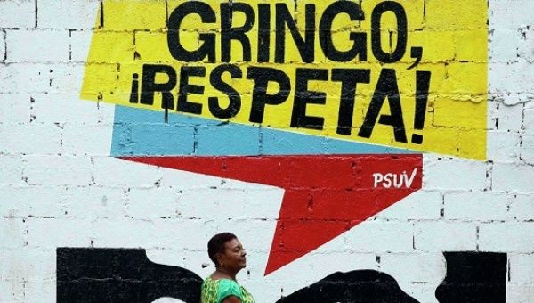 "A woman walks by a sign of the United Socialist Party in Venezuela that reads: ""Gringo Respect!""."