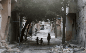 Children walk near garbage in al-Jazmati neighborhood of Aleppo, Syria April 22, 2016.