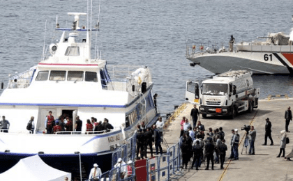 Migrants are escorted by police officers as they disembark from a ferry at a port in the Turkish coastal town of Dikili, Turkey, April 8, 2016.
