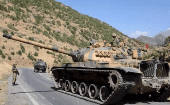 Turkish soldiers in a tank and an armored vehicle patrol on the road to the town of Beytussebab in the southeastern Sirnak province, Turkey, Sept. 28, 2015.
