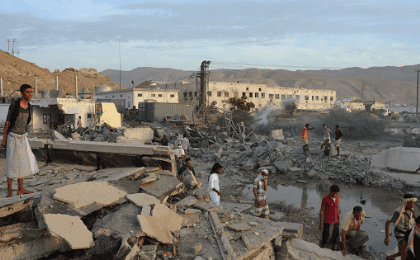 People inspect damage at a site hit by Saudi-led air strikes in the al Qaeda-held port of Mukalla city in southern Yemen April 24, 2016