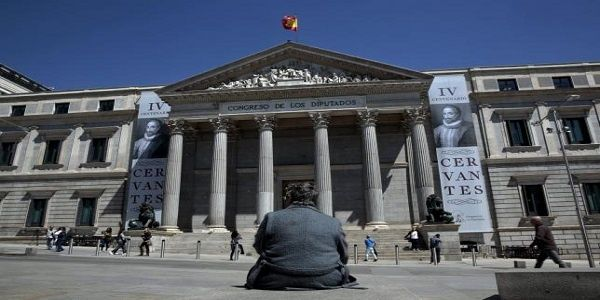 A woman sits in front of Spanish parliament in Madrid, Spain, April 25, 2016.