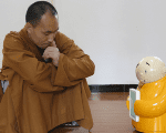 Master Xianfan looks at robot monk Xian'er as he demonstrates the robot's conversation function during a photo opportunity in Longquan Buddhist temple on the outskirts of Beijing, April 20, 2016.