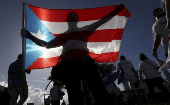 A protester holding a Puerto Rico's flag takes part in a march to improve healthcare benefits in San Juan, Puerto Rico, Nov. 5, 2015.