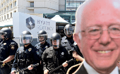 Police form a scrimmage line behind a picture of Democratic presidential candidate Sen. Bernie Sanders outside the California Republican Party convention in Burlingame, California April 29, 2016.