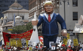 People march with an inflatable effigy of Republican presidential candidate Donald Trump during an immigrant rights May Day rally in Los Angeles, California, U.S., May 1, 2016.