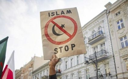"A protester from a far-right organization holds up a sign which reads ""Islam Stop"" during a protest against refugees in Lodz, Poland.."