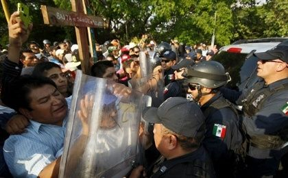 "Migrants scuffle with Mexican riot police at their annual human rights protest April 15, 2015. The writing on the cross reads ""Enough of migrant"